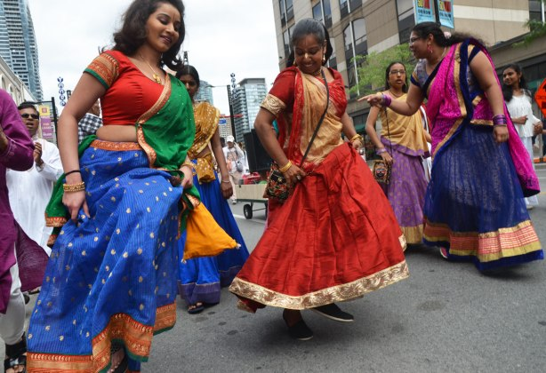 South Asian, Indian, women, in long colourful sarees dancing as they move down Yonge Street in a parade, lifting their skirts a little bit as they move