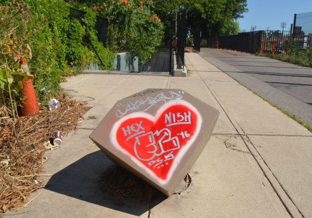 a bright red heart painted on a man made boulder, words hex and nish written on it