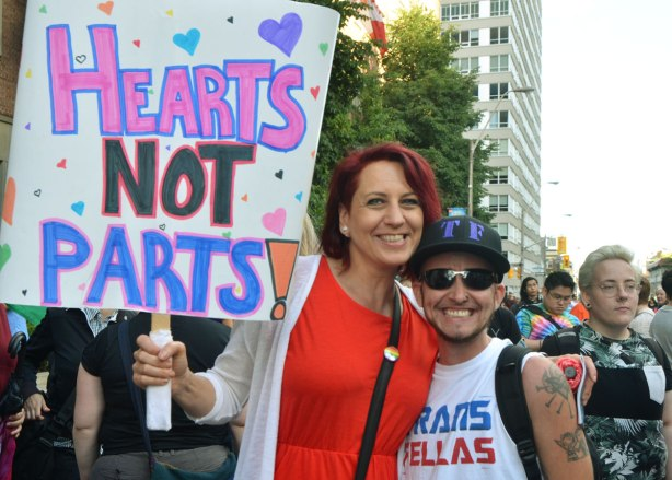 "a woman in an orange dress holds a sign that says ""Hearts not parts"", she has her arm around a young man in a black baseball cap and sunglasses."