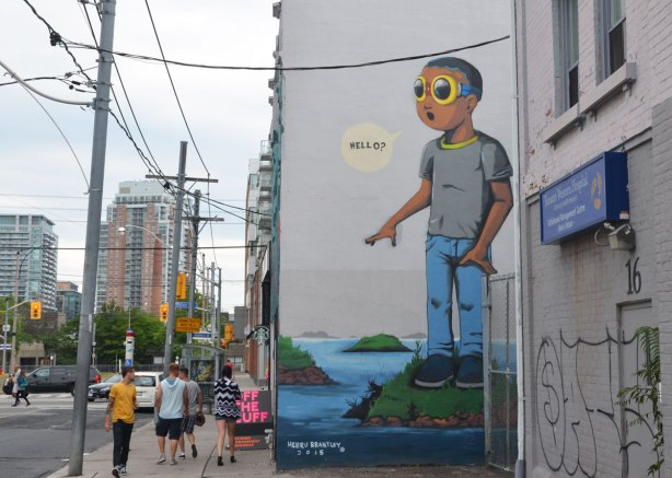 "a large mural of a boy standing on a small island, wearing sunglasses, and saying ""Hello"", painted by Hebru Brantley"