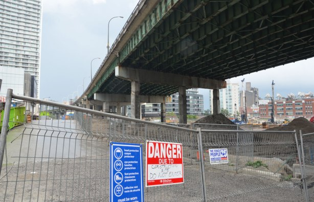 the elevated road, the Gardiner Expressway passes over a construction site on the right, a new street being built on the left.