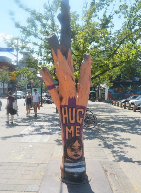 large tree stump with some of the large branches, painted an orangish brown colour with a face and the words 'hug me' on a downtown sidewalk inToronto (Queen Street West)