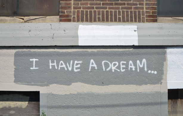 "graffiti on a wall, in white paint on grey wall, the words ""I have a dream'"