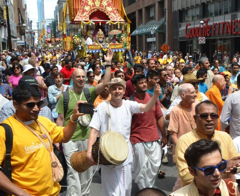 people walking in front of one of the chariots in the Festival of India parade in Toronto