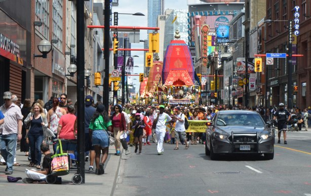 a police car drives slowly in front of a parade as it makes its way down Yonge Street