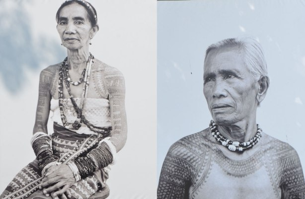 two older women with their shoulders tattooed, wearing necklaces and a patterned skirt, seated. Black and white