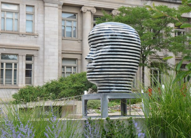 large striped head sculpture on a table, outside, by Jun Kaneko, old building behind it, lavender and other plants growing in front of it.