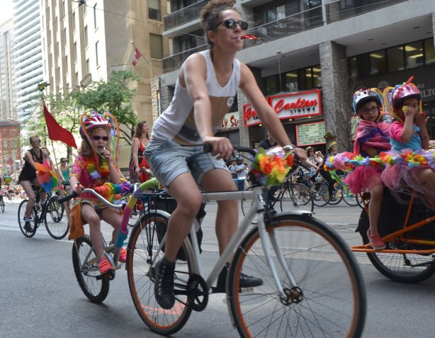 kids riding on bikes with their mothers in a dyke march