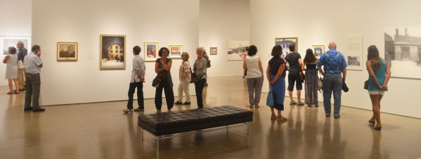 many people in a room in an art gallery, standing around and looking at paintings.