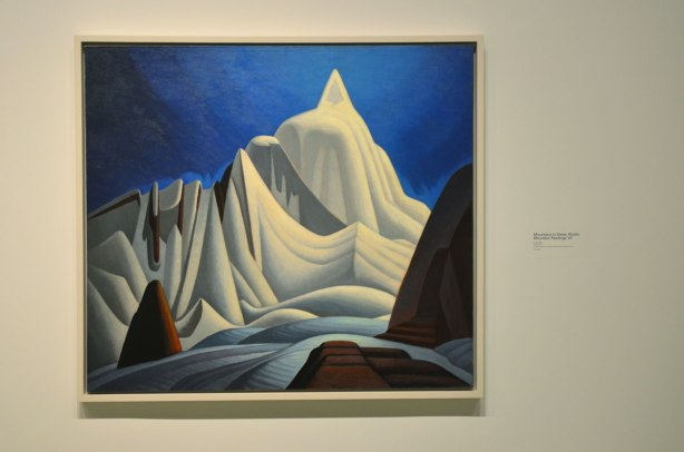 a Lawren Harris painting of a snow covered mountain, blue sky in the background.
