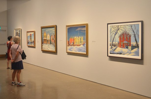 two women look at a line Lawren Harris paintings of brightly coloured houses in winter on a wall in an art gallery