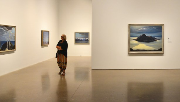 a woman walks through a gallery with paintings on the wall. She stops to look at one of them.