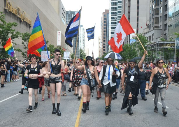 walkers in a dyke march in Toronto - a group in various leather clothes, some topless