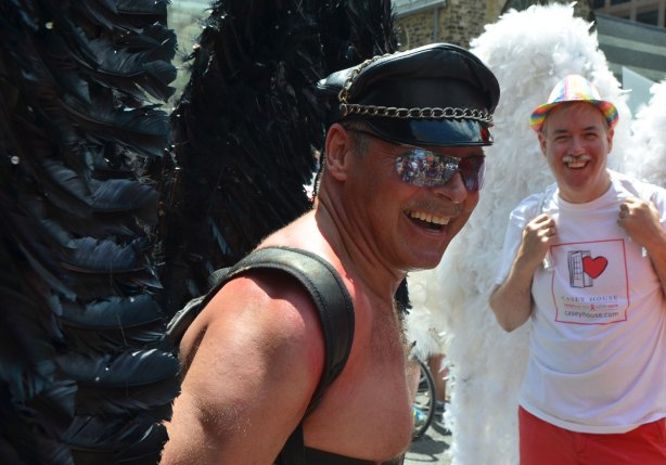 Two men with large feathery wings on their back. The one in front has black wings and is wearing a black leather hat. He is topless. The other man is wearing a white T-shirt and white feathery wings as well as a rainbow striped hat.