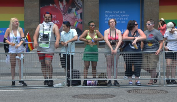line of people waiting behind barricades at the side of the street waiting for the Pride parade to begin.