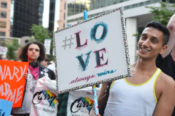 a young man in a white sleeveless shirt in a parade, holding a sign that says #love always wins