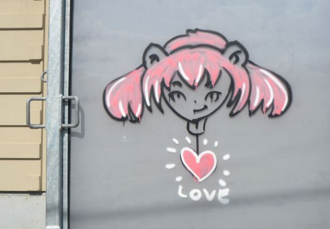 graffiti on a grey metal door of a girl's head with lots of pink hair. A pink heart beneath her with the word love under that