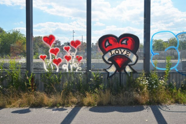 two street art pieces painted on a glass wall. the first is a red and black heart with a white banner across it on which the word love is written. the other is 8 little red hearts on white stems growing from the ground below.