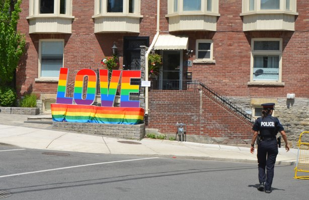a rainbow coloured large sign that says LOVE on it, in front of a row of brick houses. A policeman is walking along the street in the right of the picture