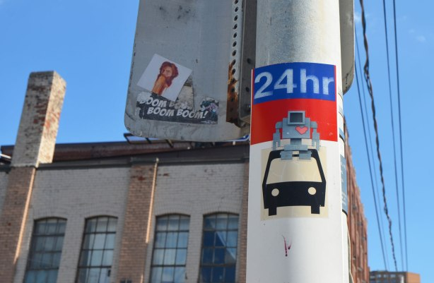 a lovebot sticker on a TTC bus stop pole, between the sign that says 24 hours and the symbol of a bus, older industrial building behind it.