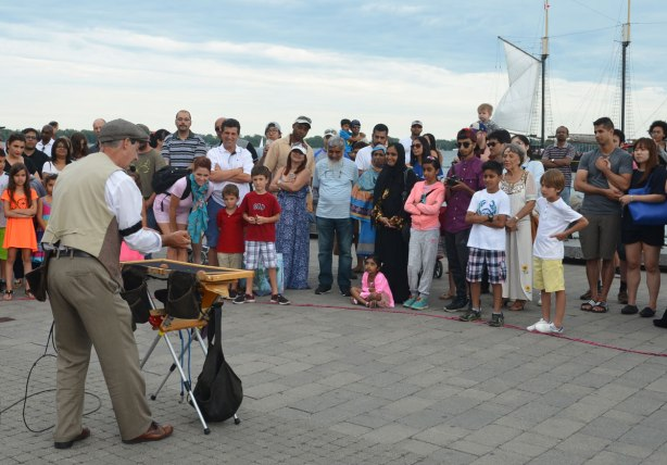 a magician entertains a crowd on the waterfront, many people are watching, men, women and kids