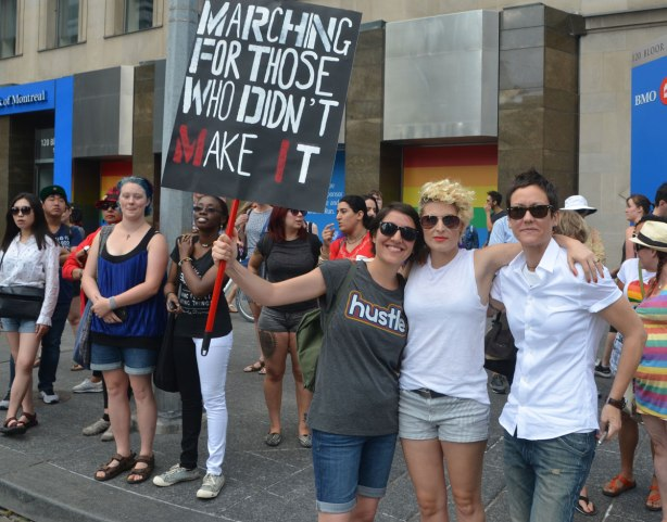 "spectators on a sidewalk watching the Dyke March, one woman has a sign that says ""Marching for those who didn't make it"""