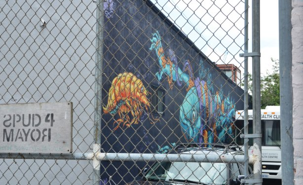 a mural of marine animals on the side of a building, but behind a locked fence