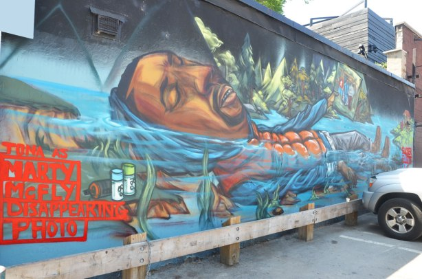mural of a man lying on his back in the water, words written in red Tona as Marty McFly