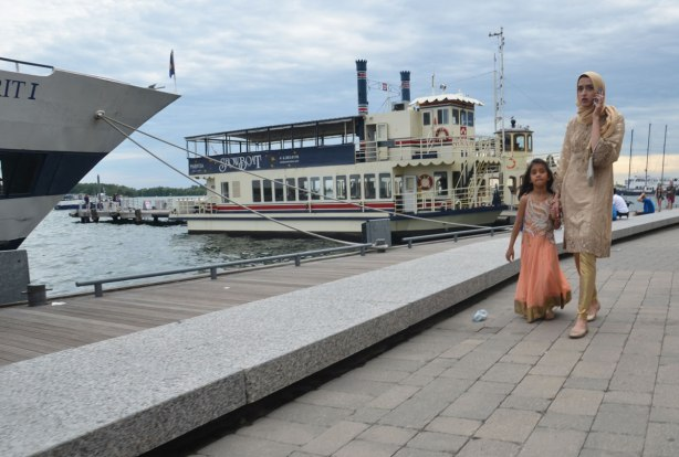 A mother and daughter in sarees walk hand in hand along the waterfront. Paddle wheeler boat for scenic tours behind them, mother on a phone