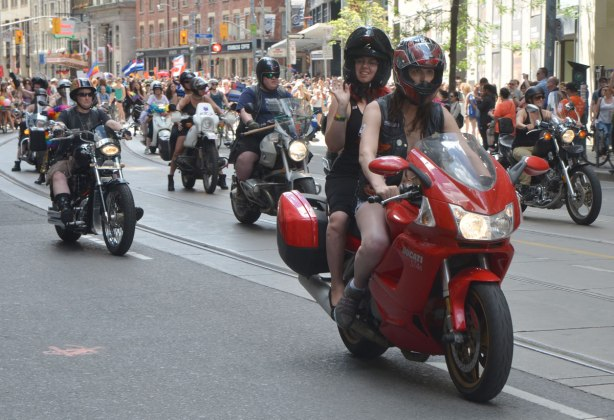 two women on a red motorcycle in a parade