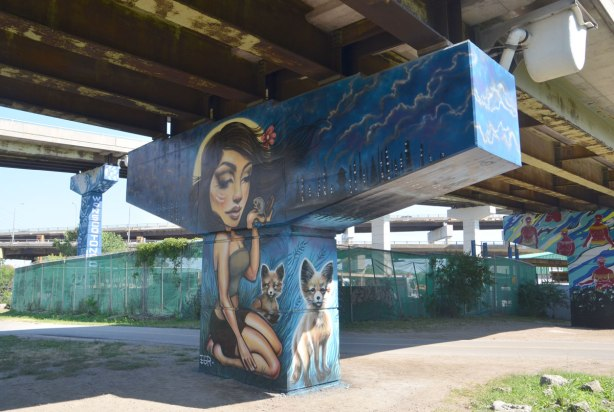 A mural on a bent in an underpass, a young woman is kneeling. She is holding a mouse in one hand. Two foxes stand beside her.