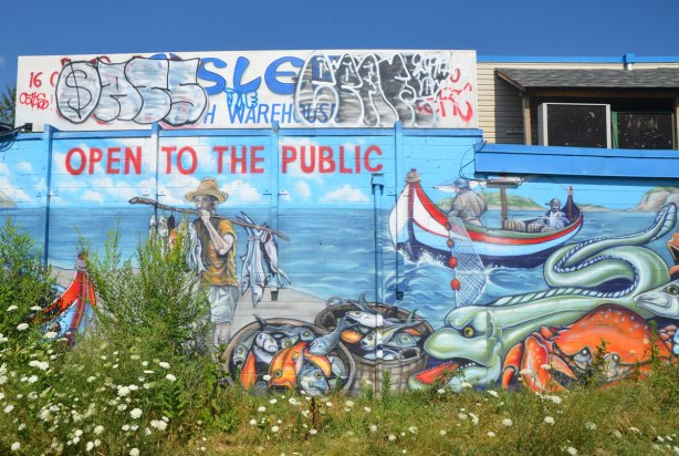 mural with fisherman bringing in a load of fish to the shore, boat in the background, more fish in the foreground.