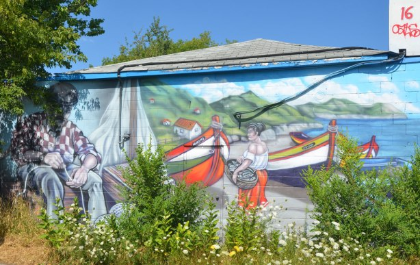 mural, man sitting, mending fishing nets, woman on the shore carrying a bundle towards some fishing boats.