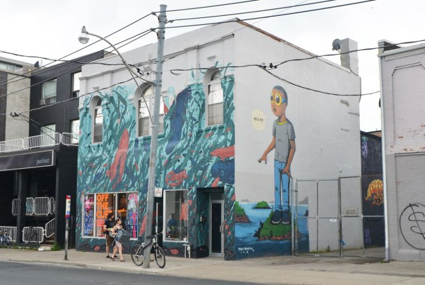 "two sides of a building with murals, one side is a large mural of a boy standing on a small island, wearing sunglasses, and saying ""Hello"", painted by Hebru Brantley and the other side (store front)"