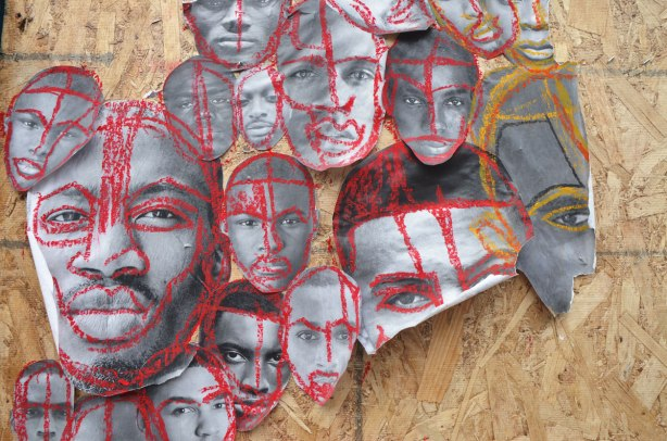 pictures of the faces of black men attached to wood construction hoardings and rough outlines and highlights drawn on the faces with crayon, in red, blue, yellow and green.