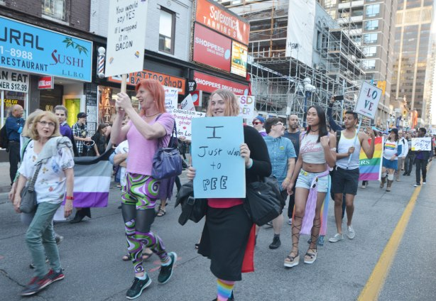 "a crowd of people walking down Yonge street in a trans parade as part of Pride, one person is holding a sign that says ""I just want to pee"""