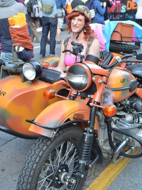 an old motorcycle and sidecar painted splotchy orange with a person wearing a pink bra sitting in the sidecar. Parked, waiting for the start of a parade.
