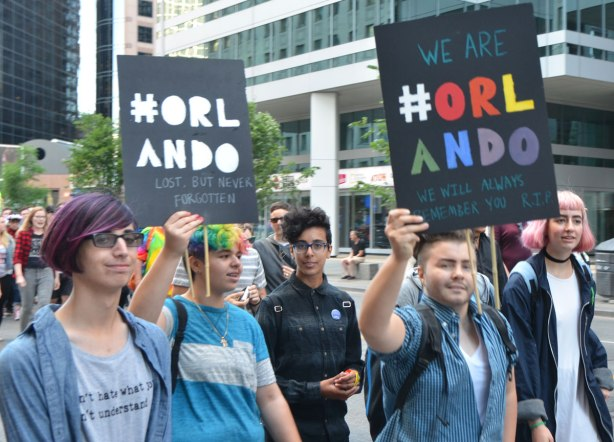 "guys walking in a trans parade on Bloor street holding signs that say ""We are #orlando, we will always remember you RIP"""