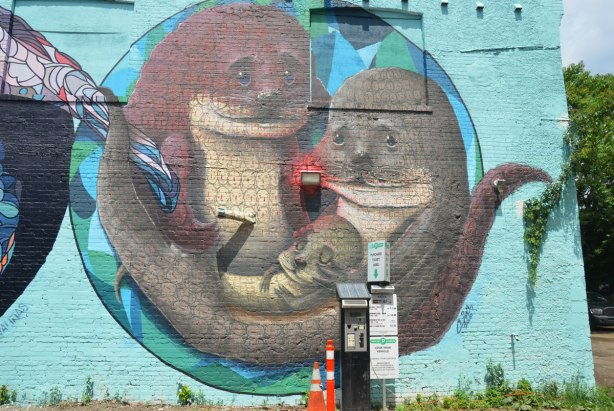 a large round mural of a family of otters. Baby otter is sleeping in his parents' arms. by Valinas