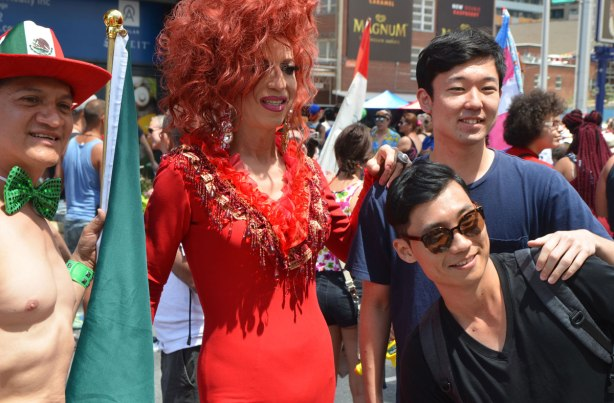 two young Asian men pose beside a man in drag, long auburn hair and a red tight fitting dress, there is also a topless man wearing a hat with a Mexican symbol on it and holding a Mexican flag.