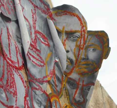 pictures of the faces of black men attached to wood construction hoardings and rough outlines and highlights drawn on the faces with crayon, in red, blue, yellow and green. Some of the faces are peeling away at the edges and the look a bit 3D