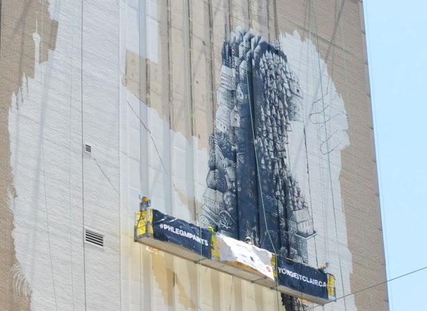 a very large mural on the side of a building is in the process of being painted. An white outline of a seated person with their knees drawn up, one leg has been painted with a design in black