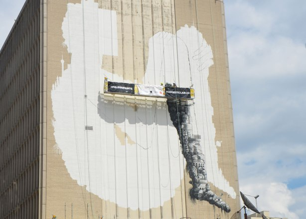 a verylarge mural on the side of a building is in the process of being painted. An white outline of a seated person with their knees drawn up, one leg has been painted with a design in black
