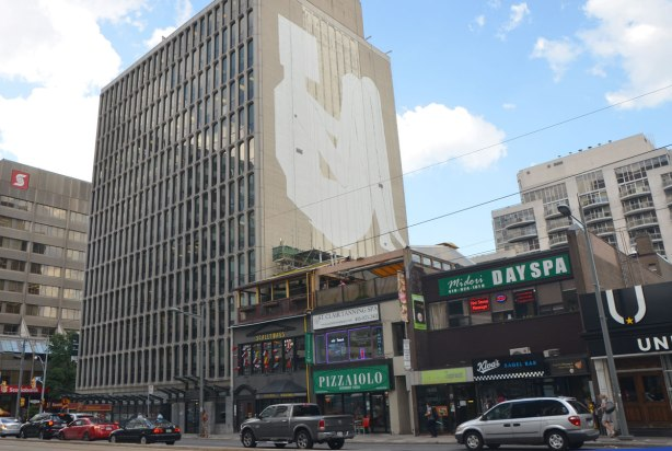 a street in Toronto, St. Clair Ave., with an older nine storey building with concrete facing, on the side, above the level of the stores beside it, is the outline of the start of a mural. All painted white, a seated figure.