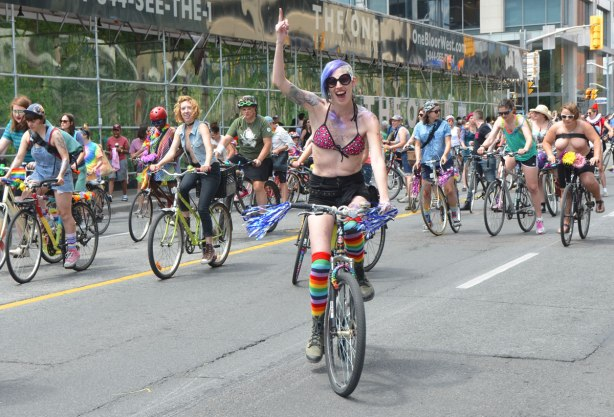 walkers in a dyke march in Toronto - Dykes on bikes, one woman on a bike has one arm in the air,