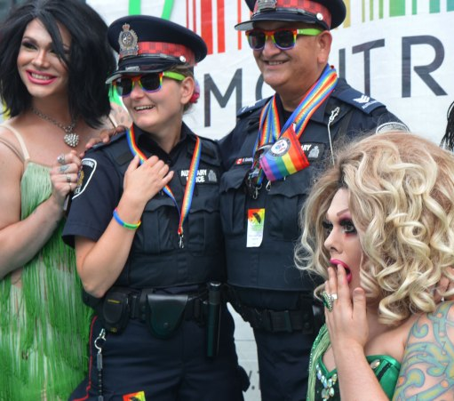 Pride weekend, two policemen with rainbow sunglasses and small rainbow flags pose with two men in drag, wearing green dresses, one in a curly blond wig and the other in a black wig