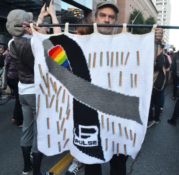 Dave holding up a large crocheted banner with a black and grey ribbon, and rainbow ribbons with the names of each of the people killed at the Pulse nightclub in Orlando.