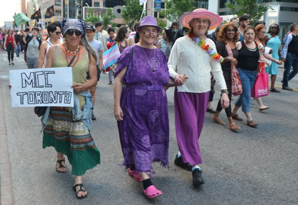 a group of people walking in a trans march, three in long skirts and two with hats, the middle one is dressed all in purple