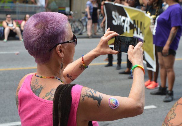 a woman with very short purple hair, a pink sleeveless top, and many tattoos, is taking a picture with her phone of a group marching in the Dyke March