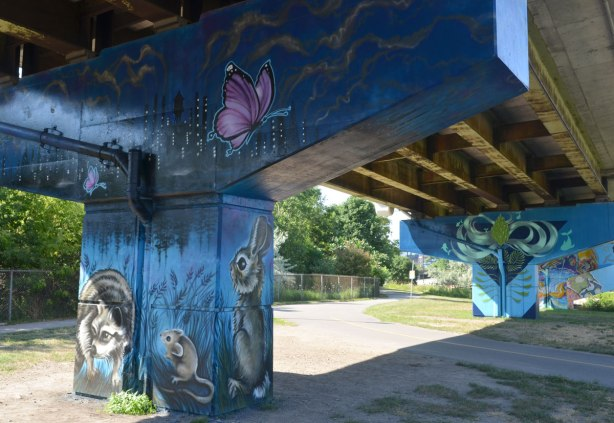 2 bents covered with murals. In the foreground, the mural is dark blue, with a pink butterfly, a rabbit, a mouse and a raccoon.